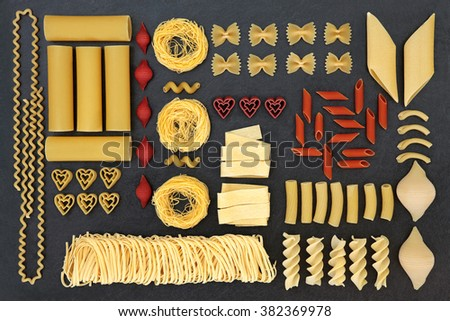 Large dried pasta selection with tomato and beetroot coloured varieties over slate background. - stock photo