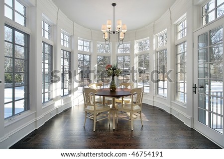 Large eating area with wall of windows in luxury home - stock photo