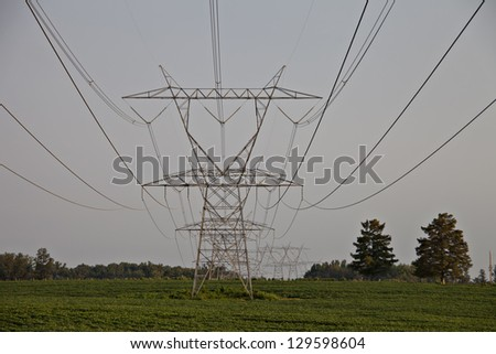Large electrical towers in lush green field with power lines leading the eye to towers. - stock photo
