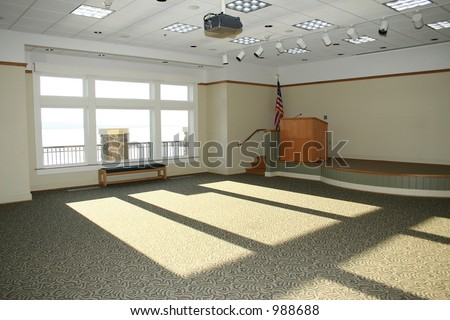 Large empty meeting room with stage, podium, American Flag.