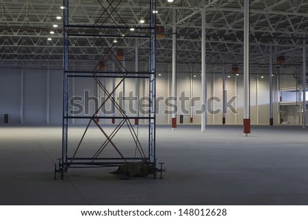Large empty storehouse with scaffold