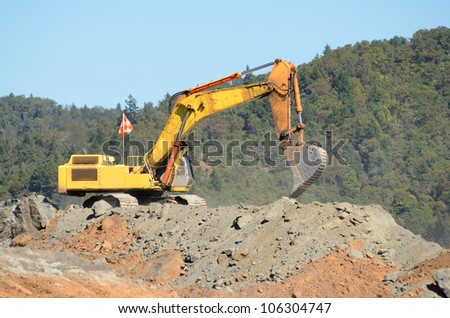 Large excavator loading articulating dumps at an airport runway extension project
