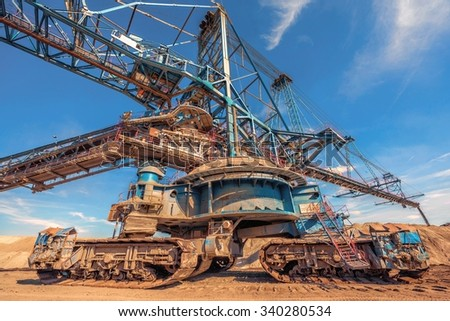 Large excavator machine in the mine working - stock photo