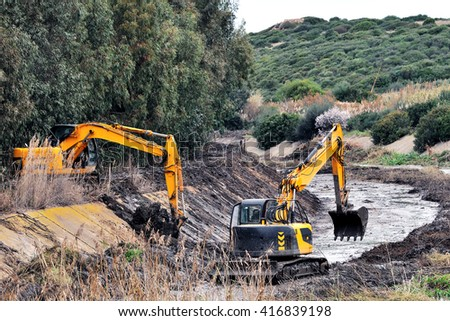 Large excavators engaged in cleaning of the riverbed of a river from the mud and debris. - stock photo