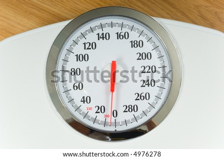 Large face bathroom scale with dial and chrome finishing around face - stock photo
