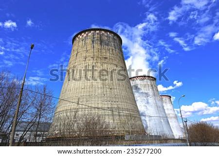 Large factory chimneys on blue sky background - stock photo