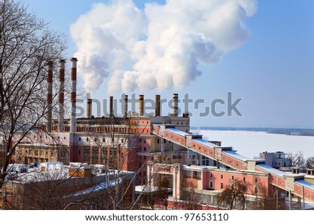 Large factory with smoking chimneys against the blue sky - stock photo