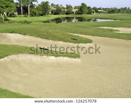 Large fairway bunker near pond on golf course in Florida - stock photo