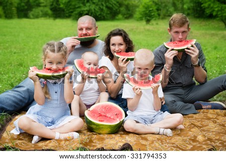 Large family eating watermelon in the summer park