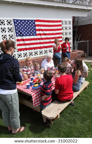 Large family gathering for a 4th of July barbecue - stock photo