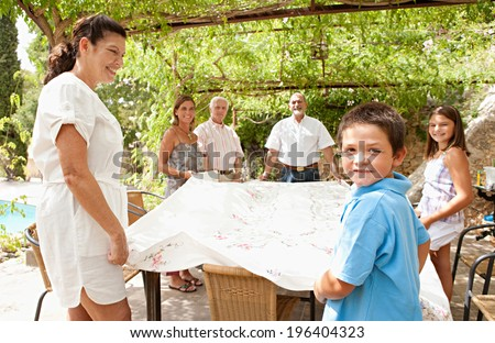 Large family group setting up a table cloth together in teamwork, getting ready for eating lunch outdoors during a sunny day on holiday in a summer villa vacation home garden, relaxing lifestyle.