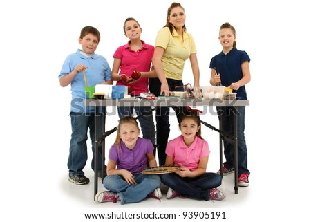 Large family of six children baking cookies together over white background.