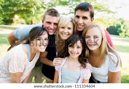 large family outside together smiling - stock photo