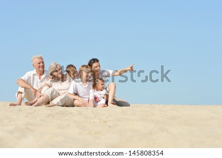 large family resting on the sand in the summer together