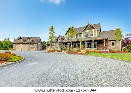 Large farm country house with gravel driveway and green landscape. - stock photo