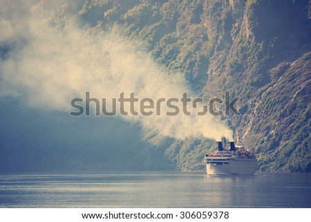 large ferry in the most beautiful Geiranger fjord in Norway - stock photo
