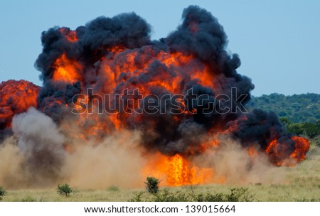 Large fireball with black smoke in bushy hills - stock photo