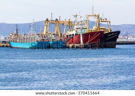large fishing ship factories at anchor in harbor showing large infrastructure and equipment to net fish from the oceans - stock photo