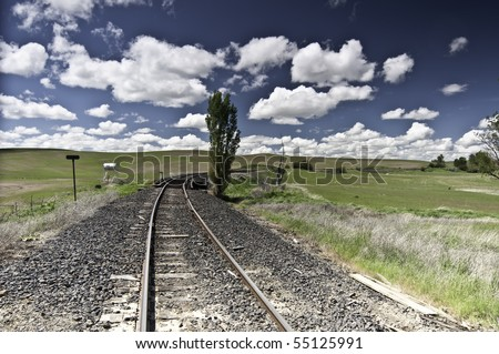 Large fluffy clouds with train track and open farm fields. - stock photo