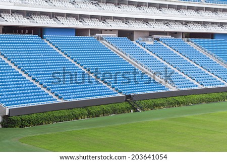 Large football stadium with green grass and blue seats