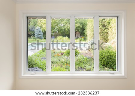 Large four pane window looking on summer backyard with pool and garden