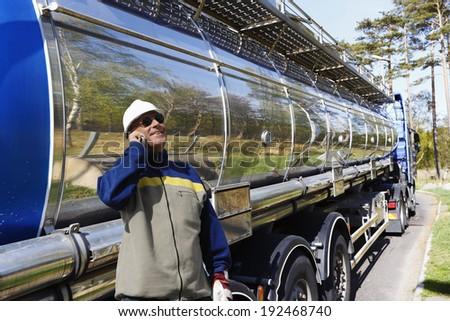 large fuel and oil truck with driver talking in phone after re-fueling. - stock photo