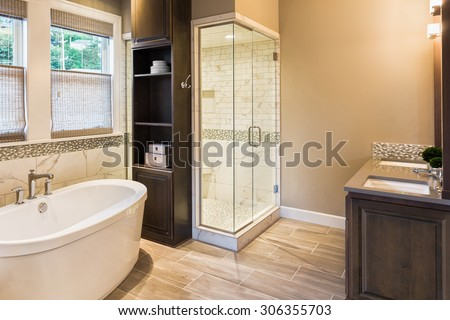 Large furnished bathroom in luxury home with tile floor, fancy cabinets, large mirror, shower, and bathtub