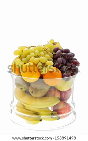 large glass bowl of various fruits on a white background
