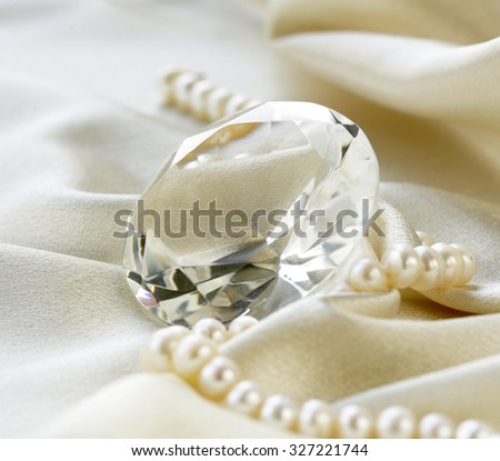 large glass diamond and pearl necklace on a soft silk background - stock photo