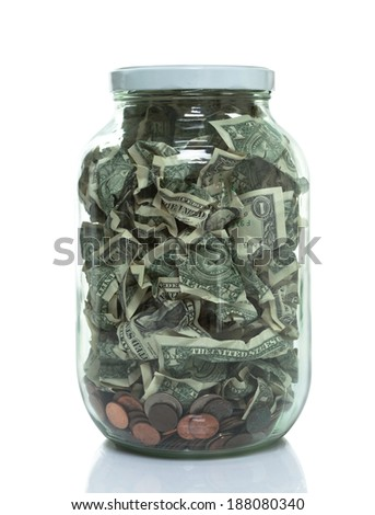 Large glass jar full of money - stock photo