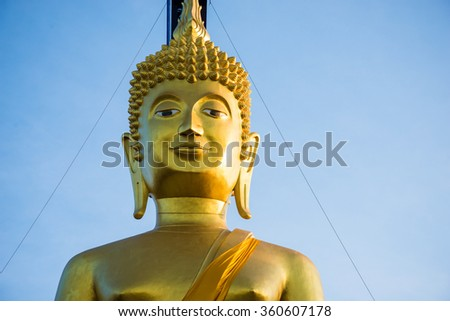 Large golden buddha statue on blue sky - stock photo