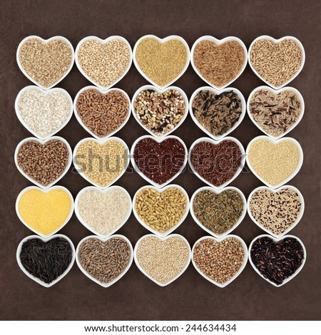 Large grain and cereal food selection in heart shaped porcelain bowls over lokta paper background. - stock photo