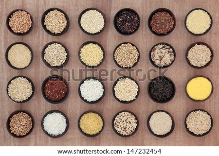 Large grain and cereal selection in wooden bowls over papyrus parchment background. - stock photo