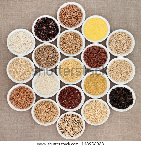 Large grain food selection in white porcelain bowls over hessian background. - stock photo