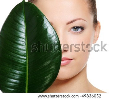 Large green leaf shading a half of beautiful woman face over white background - stock photo