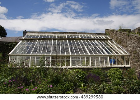Large greenhouse attached to an old garden wall
