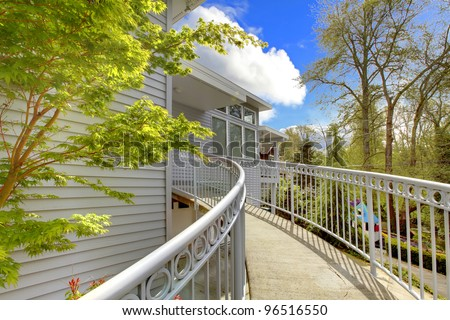Large grey house exterior of modern home with curved staircase leading to the front door. - stock photo