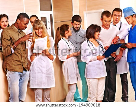 Large group doctors standing at reception in hospital. - stock photo
