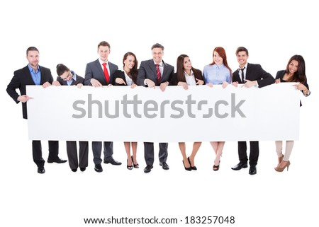 Large group of businesspeople presenting empty banner. Isolated on white - stock photo