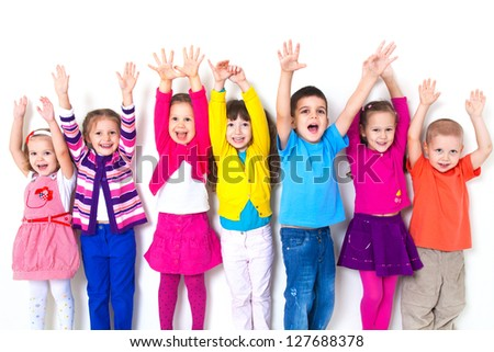large group of children happily pulled his hands up in  white wall - stock photo
