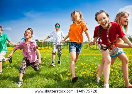 Large group of children running in the dandelion spring field - stock photo