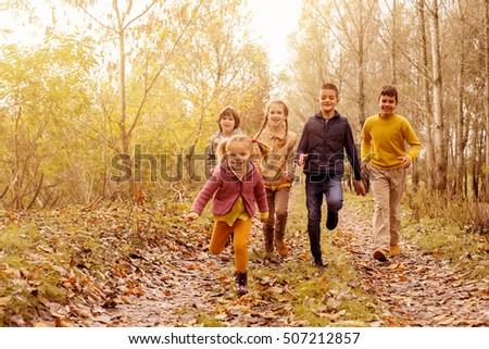 Large group of children running in the park. Autumn season.