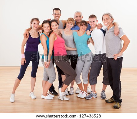 Large group of diverse male and female friends posing together at the gym in their sportswear