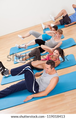 Large group of diverse people exercising in a gym class lying on blue mats doing leg raising and twisting exercises