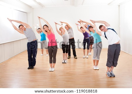 Large group of diverse people in a pilates class exercising in a gym doing core stretching - stock photo
