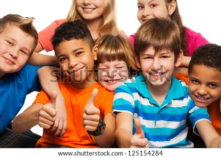 Large group of diversity happy kids boys and girls of age 8-11 years old with one of them thumbs up and smile - stock photo