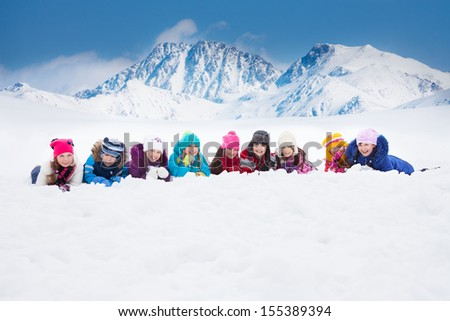 Large group of diversity looking kids 5-10 years old boys and girls on snow in a row day in mountains - stock photo