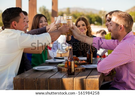 Large group of friends making a toast with beer while hanging out at a restaurant - stock photo