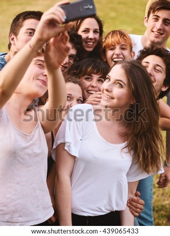 large group of friends together in a park having fun and taking a selfie with a smartphone