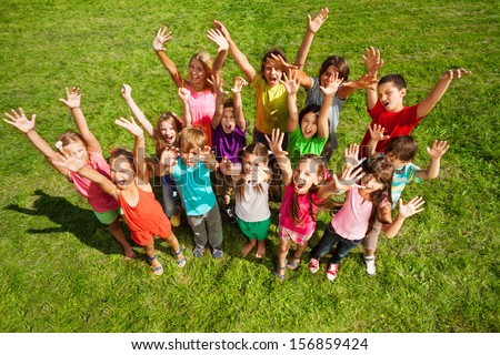 Large group of happy kids, boys and girls, with lifted hands about 10 years old standing on the green grass top view - stock photo